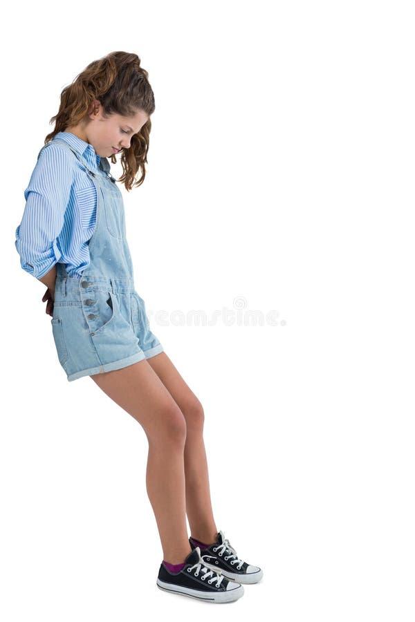 Teenage girl pushing behind against white background royalty free stock image