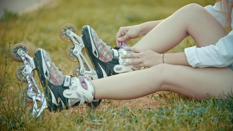 A teenage girl putting on her rollerblades stock image