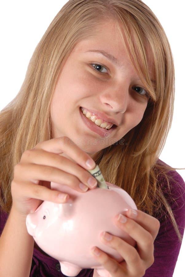 Teenage girl putting money piggy bank savings