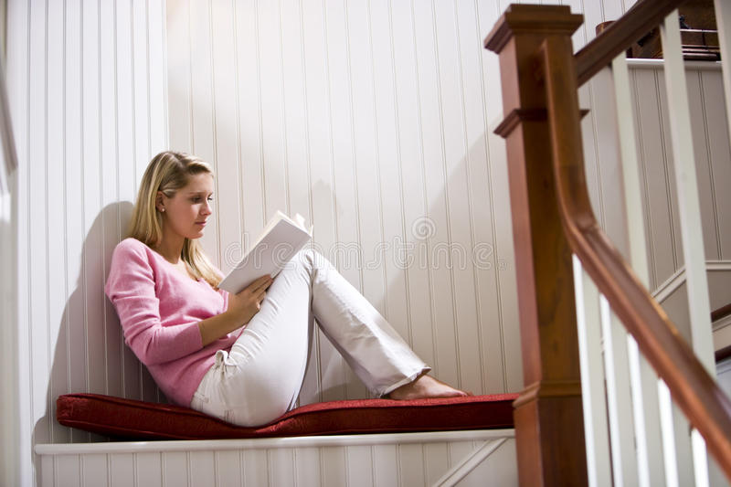 Teenage girl quietly relaxing and reading book stock image
