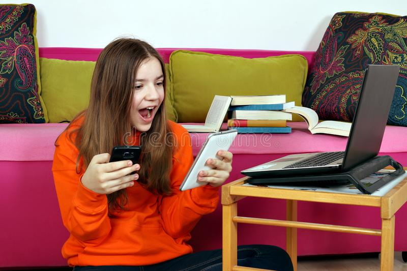 Teenage girl reading good news from messages on smartphone stock image