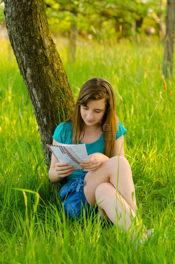 Teenage girl reading letter in the nature stock photography