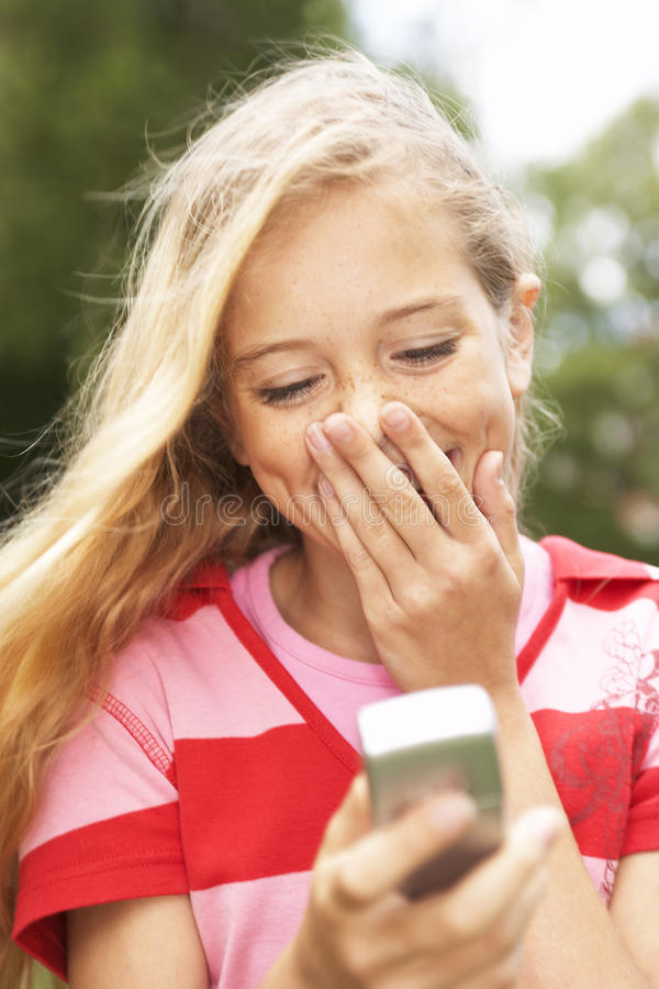 A teenage girl reading a message on her mobile phone. royalty free stock image
