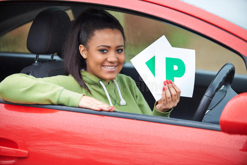 Teenage Girl Recently Passed Driving Test Holding P Plates. Happy Teenage Girl Recently Passed Driving Test Holding P Plates stock photography