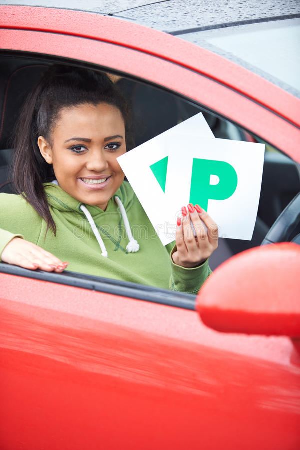 Teenage Girl Recently Passed Driving Test Holding P Plates. Smiling Teenage Girl Recently Passed Driving Test Holding P Plates stock images