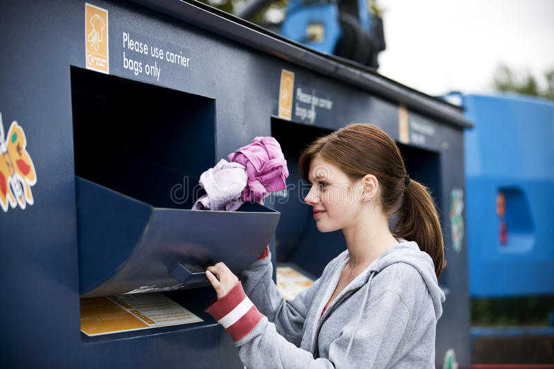 A teenage girl recycling clothes stock image