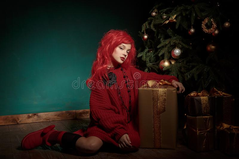 A teenage girl in a red knitted sweater and wig sits on the floor near a Christmas tree and presents. Fashion New Year stock photography