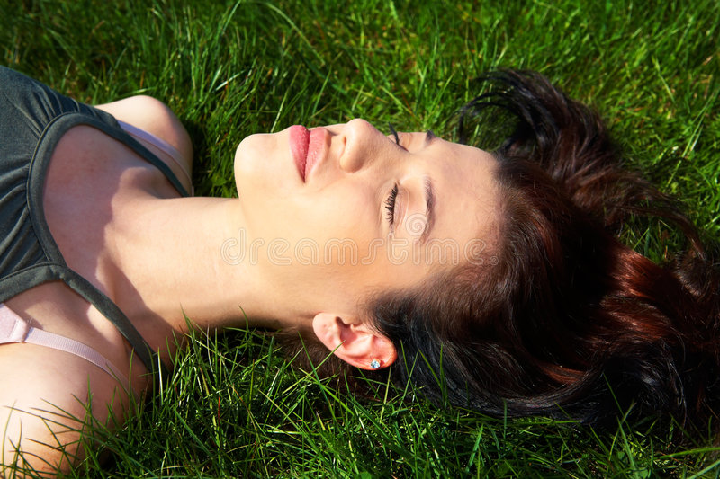 Teenage Girl Relaxing. In grass eyes closed stock photography