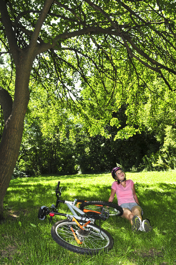 Teenage girl relaxing in a park with her bicycle. Teenage girl relaxing under green tree with her bicycle stock images