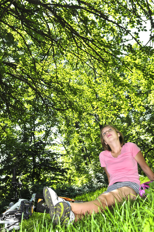Teenage girl relaxing in a park with her bicycle. Teenage girl relaxing under green tree with her bicycle royalty free stock images