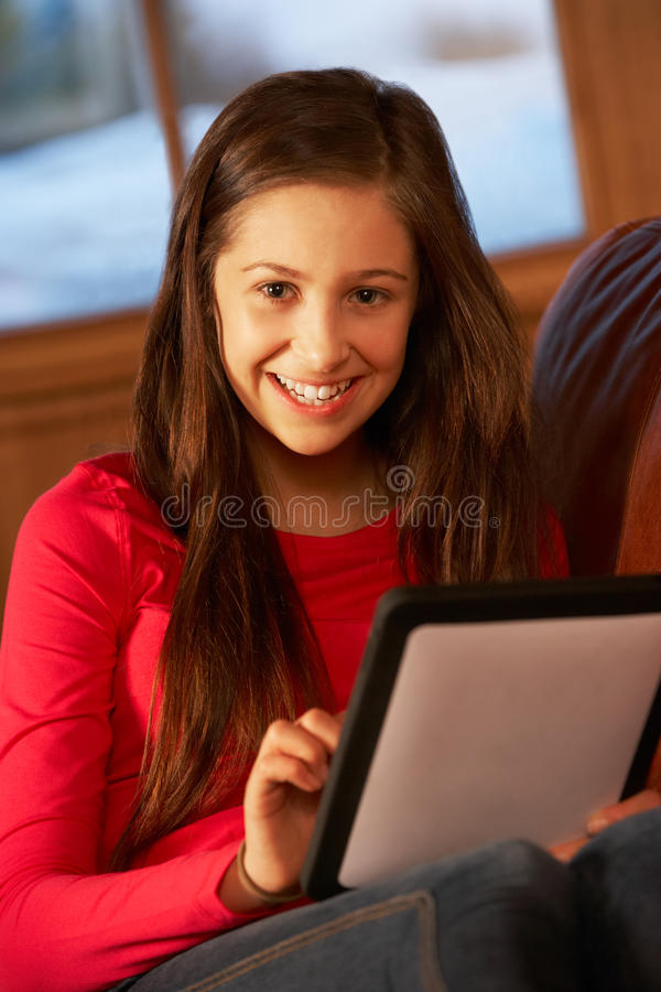 Download Teenage Girl Relaxing On Sofa With Tablet Computer Royalty Free Stock Images - Image: 25641749