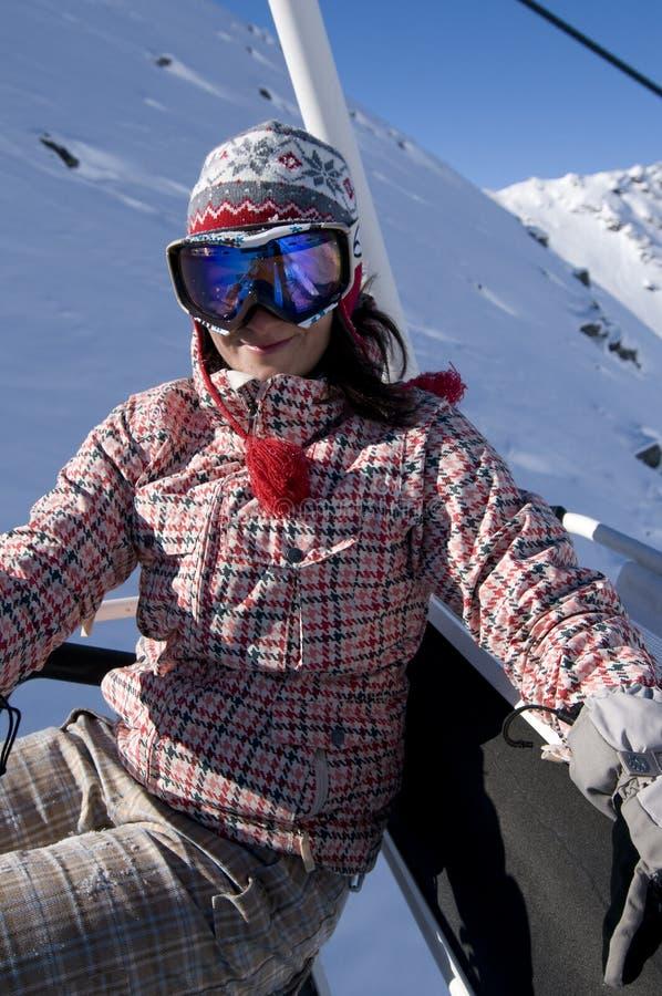 Teenage girl riding chair lift at ski resort. Caucasian teenage girl wearing goggles riding chair lift at ski resort royalty free stock photos