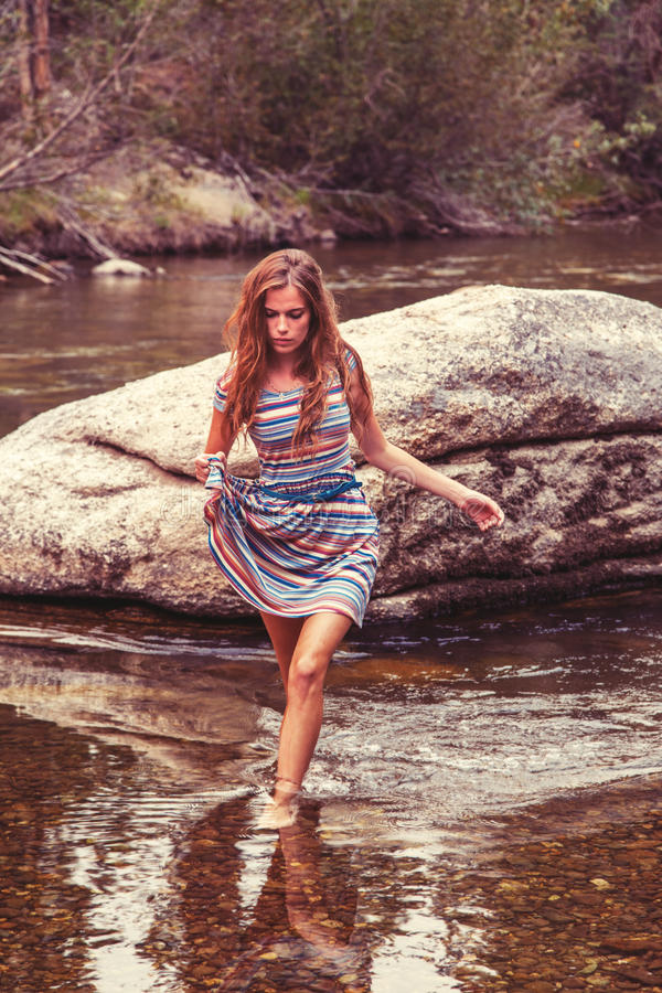 Teenage girl in river. Teenage girl in colorful striped summer dress walking from a large rock in the river to the nearest bank, forest background stock image