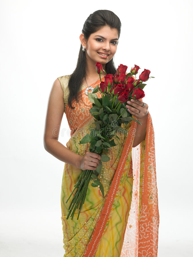 Teenage girl with roses. Teenage girl in sari with bunch of red roses royalty free stock photo