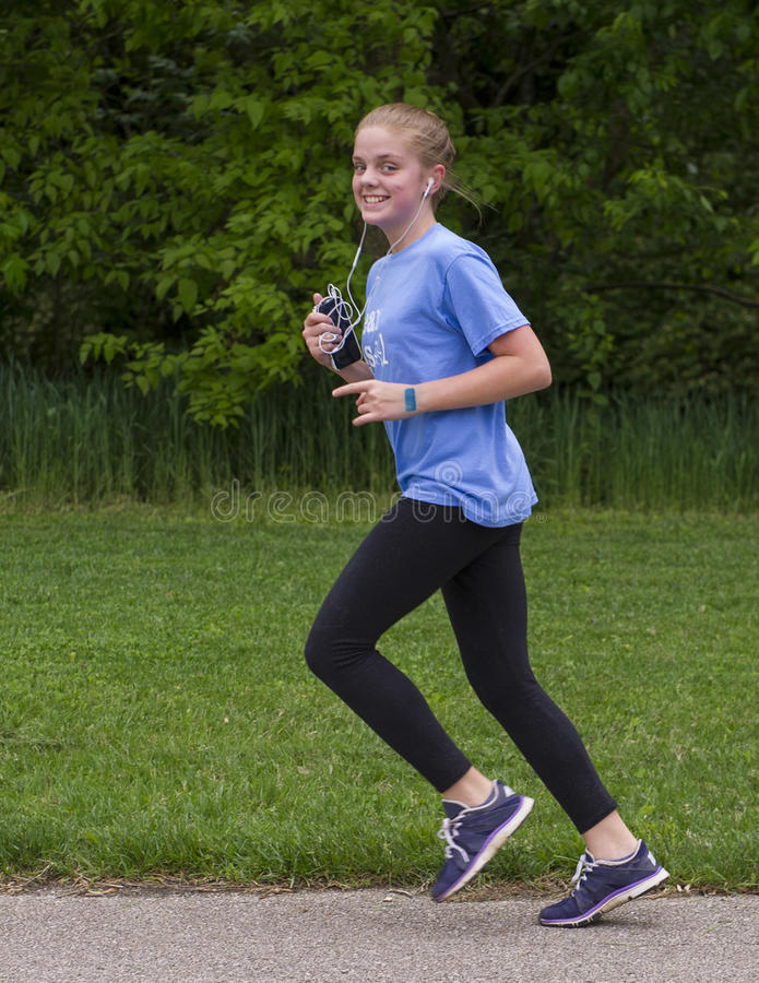 Teenage girl running. A thirteen year-old teenage girl is running along an asphalt path with green grass and trees in the background. She is listening to music stock photo