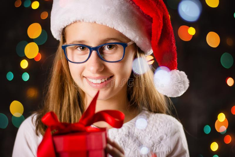 Teenage girl with Santa hat holding a present stock photo