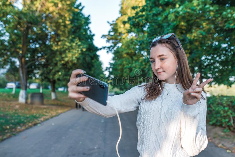 Teenage girl schoolgirl, happy smiling having fun, recording video, video call, teenager headphones taking pictures. Themselves phone, autumn summer city, white stock images