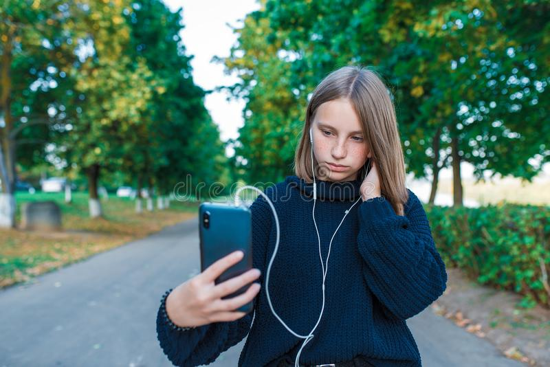 Teenage girl schoolgirl, teenager with headphones taking photos themselves phone, serious girl listens conversation. Recording, video call, autumn summer city royalty free stock photo
