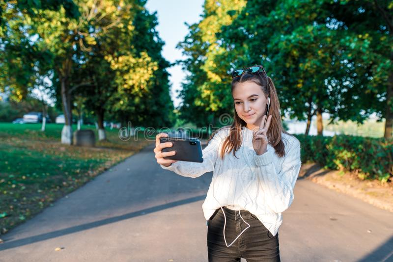 Teenage girl schoolgirl, teenager headphones taking pictures themselves phone, happy smiling having fun, recording video. Video call, autumn summer city, white royalty free stock image