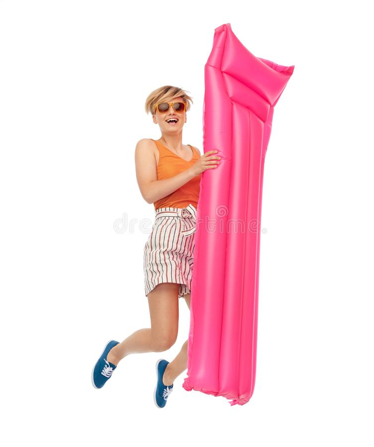 Teenage girl in shades jumping with pool mattress royalty free stock photos