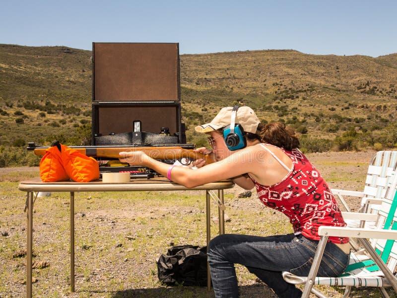 Teenage girl shooting a rifle royalty free stock image