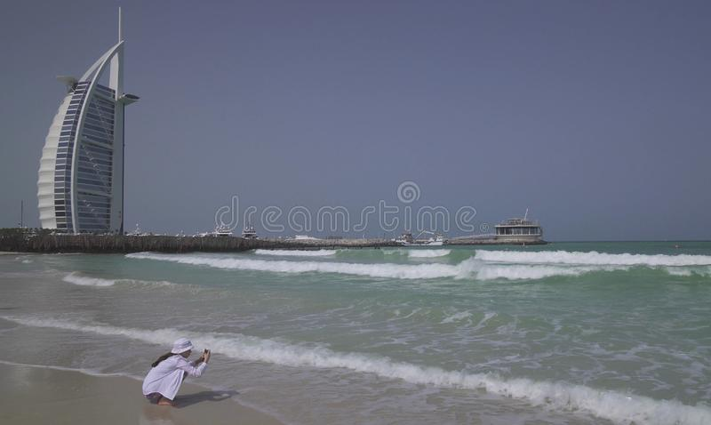 Teenage girl shoots on smartphone the sea waves on Public Jumeirah Open Beach on the coast of the Persian Gulf, Dubai royalty free stock images