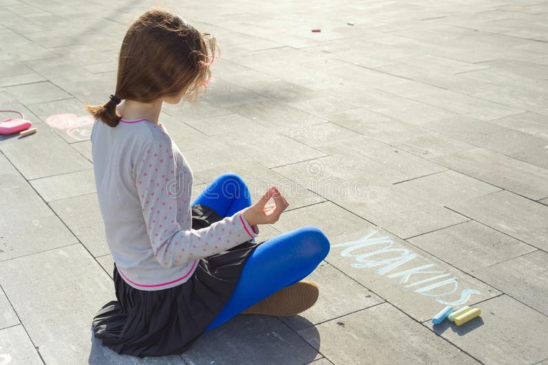 Teenage girl sits in pose meditation, practicing yoga. On the asphalt text yoga kids, written by colored crayons.  royalty free stock image