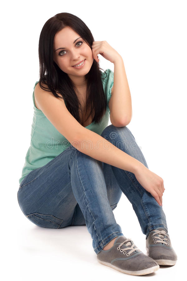 Teenage girl sitting. Portrait of teenage girl in jeans and sneakers stock photo