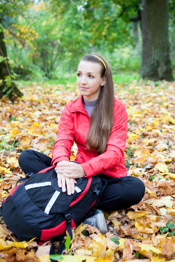 Teenage girl sitting in autumn forest stock photo