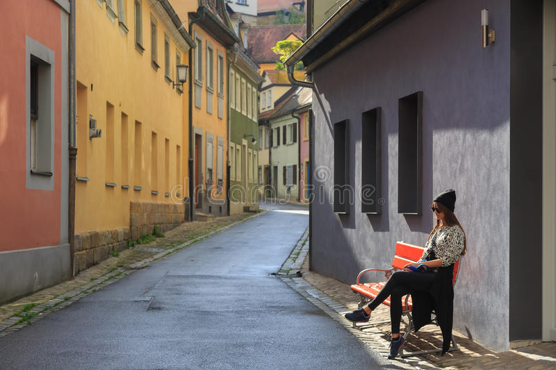 Teenage girl sitting on the bench on old city street. Bamberg, Germany stock photography
