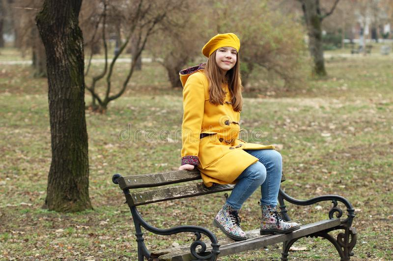 Teenage girl is sitting on the bench royalty free stock images