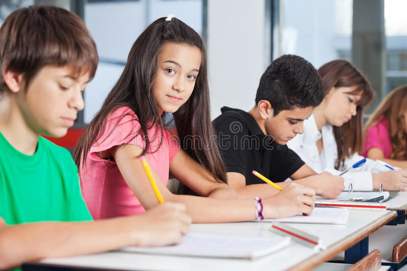 Teenage Girl Sitting With Classmates Writing At. Portrait of teenage girl sitting with classmates writing at desk in classroom stock photos