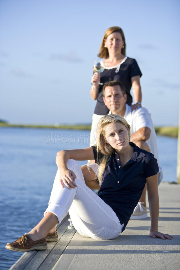 Teenage girl sitting on dock by water with parents stock photo