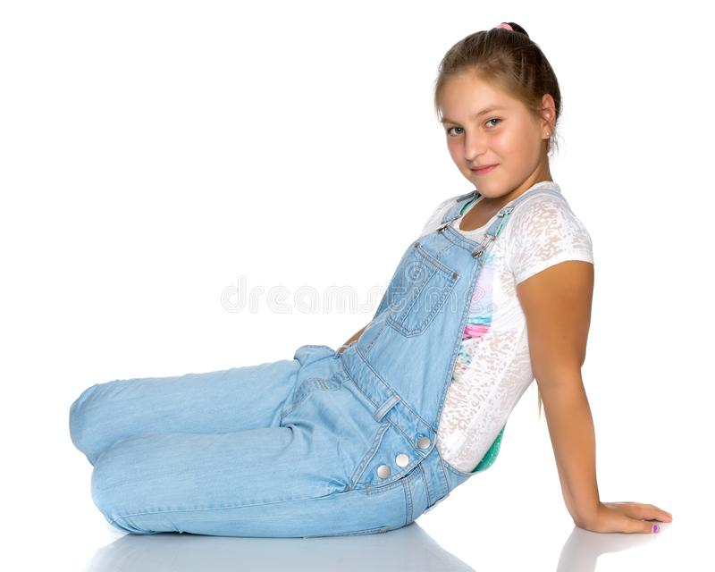 A teenage girl is sitting on the floor. stock images