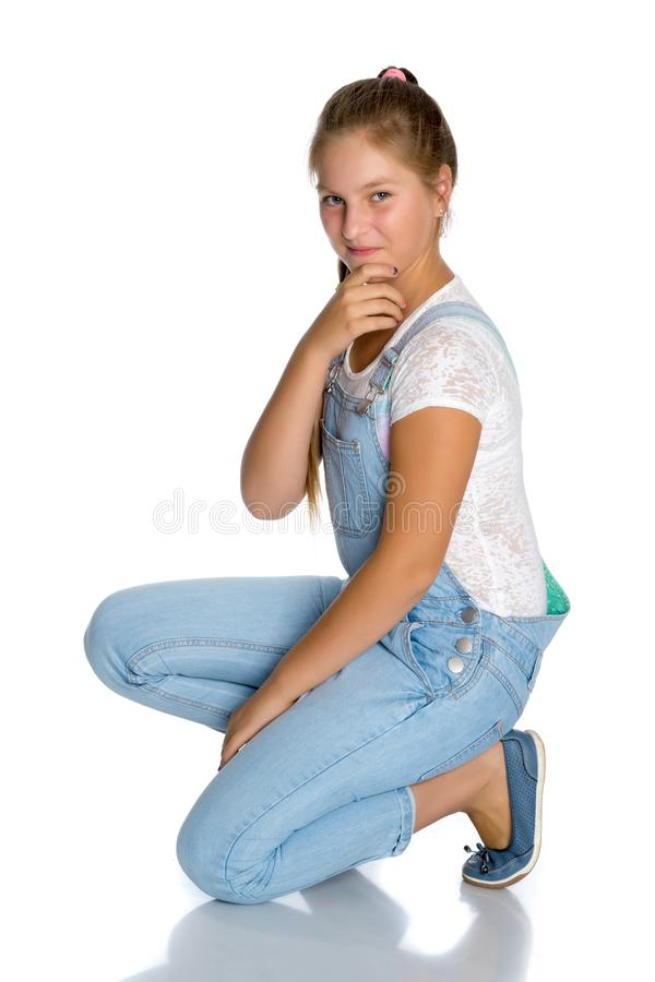 A teenage girl is sitting on the floor. On white background royalty free stock photo