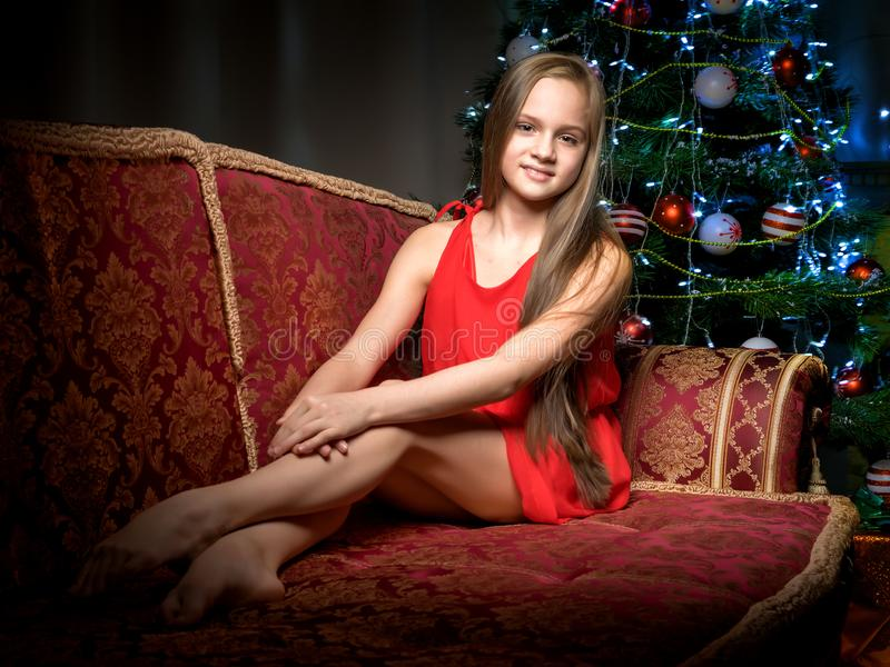 A teenage girl is sitting near the New Year tree. royalty free stock photography