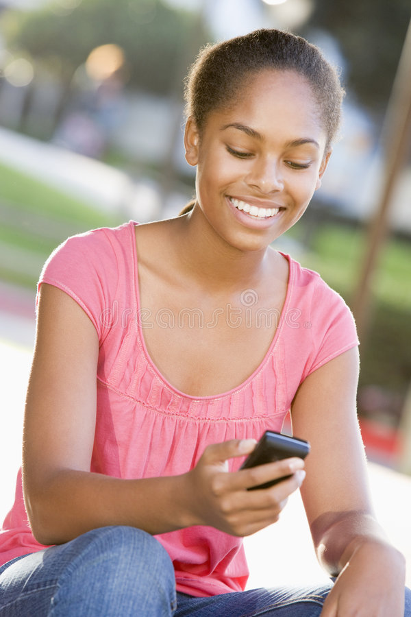 Download Teenage Girl Sitting Outdoors Using Mobile Phone Stock Image - Image: 6883925