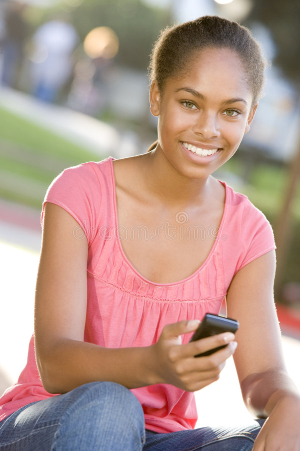 Teenage Girl Sitting Outdoors Using Mobile Phone Stock Photo