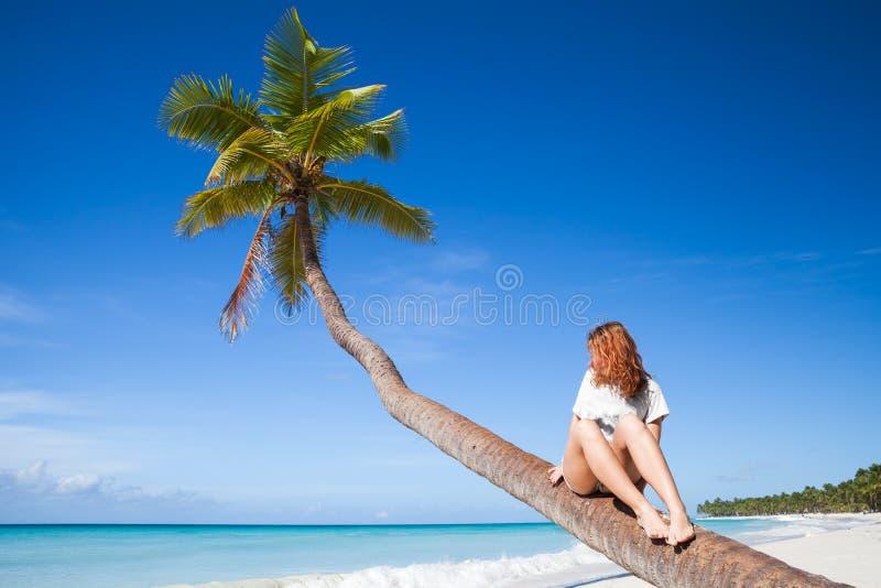 Teenage girl sitting on a palm tree. Saona island. Beach. Atlantic ocean coast, Dominican Republic royalty free stock photos