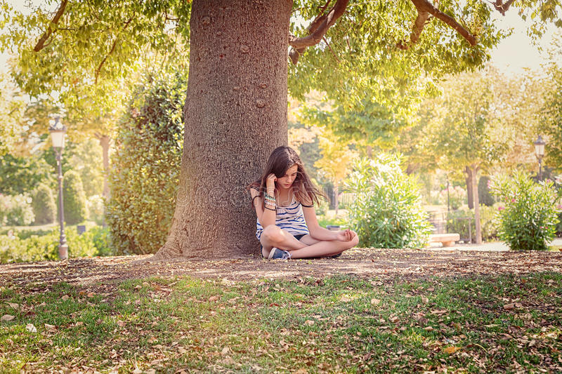 Teenage girl is sitting and relaxing under a big tree. In a park stock photos