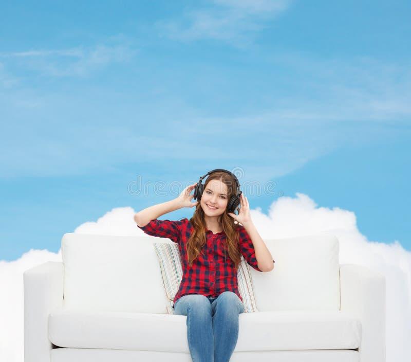 Teenage girl sitting on sofa with headphones stock images