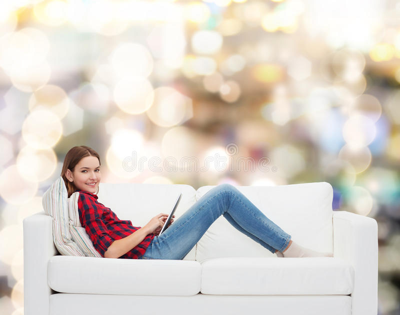 Teenage girl sitting on sofa with tablet pc royalty free stock images