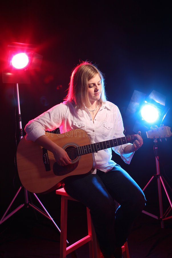 Teenage girl sitting on stage with a guitar royalty free stock photo
