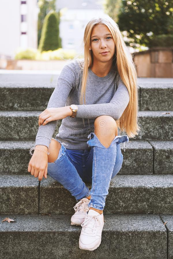 Teenage girl sitting on steps outside royalty free stock photography