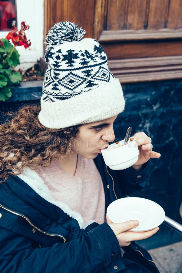 A teenage girl is sitting in a terrace and is drinking a cup of stock images