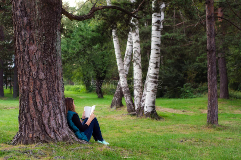 Teenage girl sitting under the tree and reading book royalty free stock photography