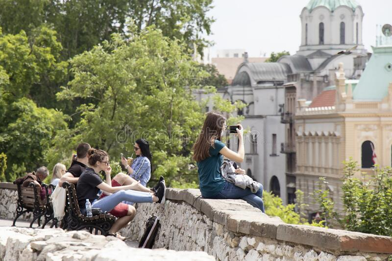 Teenage girl sitting on a wall of Kalemegdan fortress and a group of young people behind her relaxing on a bench royalty free stock photos