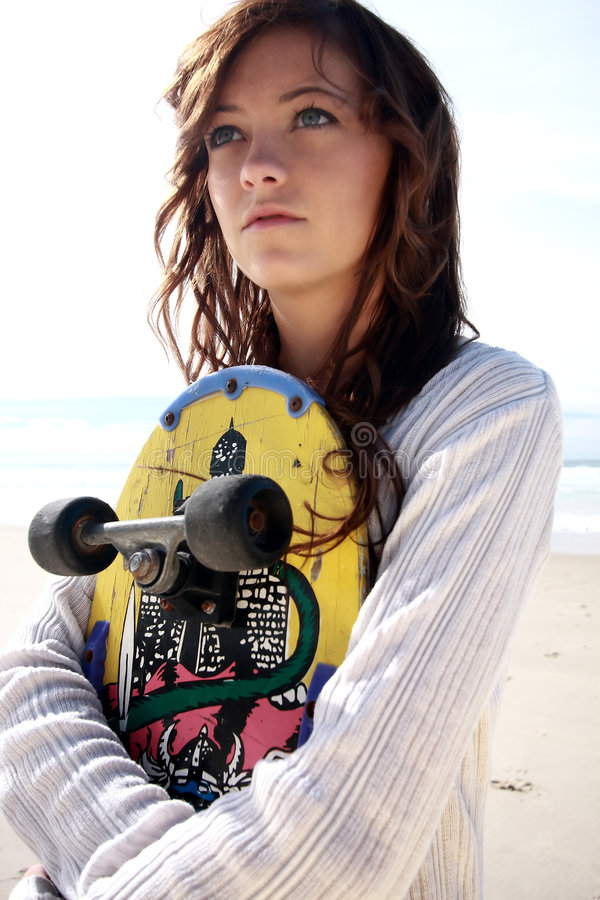Teenage girl with skate board. A teenage girl holding a skate board on the beach royalty free stock photography