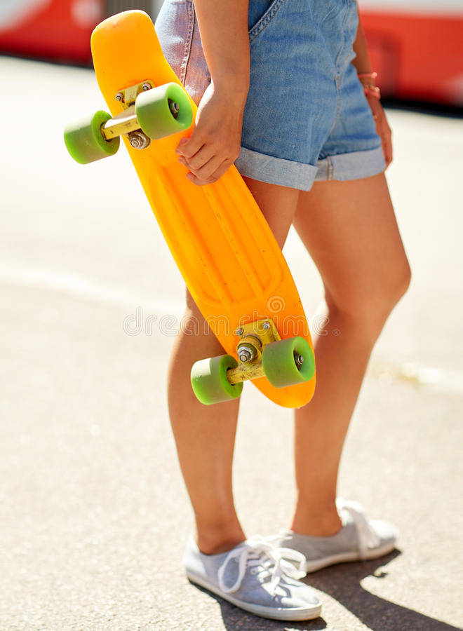 Teenage girl with skateboard on city street. Summer, extreme sport and people concept - teenage girl with short modern cruiser skateboard on city street royalty free stock photos