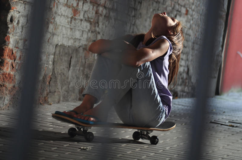 Teenage girl with skateboard in the street royalty free stock images